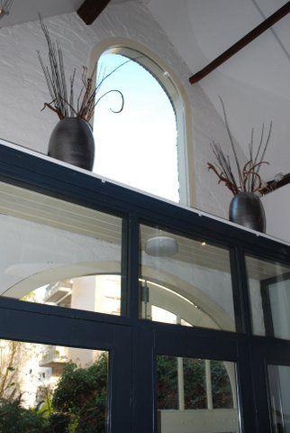 Interieuradvies werkruimte 8Ontwerp, Arnhem: De hoogte van de ramen wilde ik nog meer accentueren, dus gekozen voor mooie grote vazen met takken. Vanaf de bovenverdieping kijk je er precies op. Wil je ook advies over jouw interieur, ga naar mixinstijl.nl