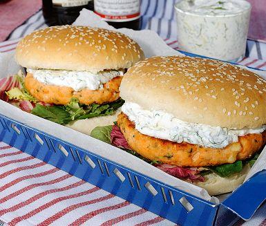 Grilla rejäla burgare på laxfärs smaksatta med fetaost och röd paprika. Använd gärna en grillbricka så håller laxburgarna ihop bättre. De maffiga burgarna serveras med en härlig tsatsiki smaksatt med färsk dill. Hamburgerbrödet kan bytas ut mot rostat surdegsbröd.