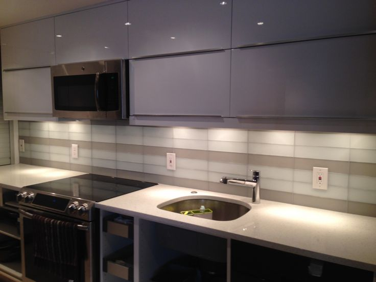 This custom designed backsplash features our 3x12 Naturals matte glass field tile in Cliff and Snow Flake. This project was selected out of our Bethesda Showroom. ...