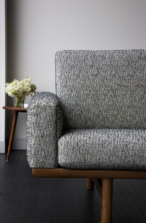 Mammoth fabric by Instyle - A sophisticated and distinctive boucle texture with a warm and inviting hand from the sustainable LIFE Textiles collection. Made from EthEco wool and eco wool, Mammoth Decision in black and white is upholstered on Danish Red sofa.