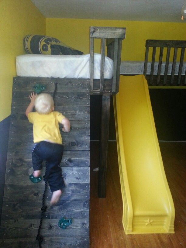 My husband made this loft bed with rock wall to get up and slide to get down