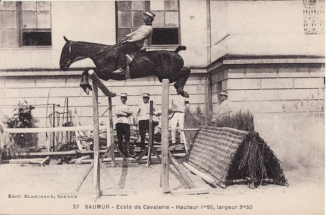 Terrible position. Amazing horse- Hard to imagine a horse being able to clear a fence of this size with its rider sitting so far back. That was the style in the early 1900s.