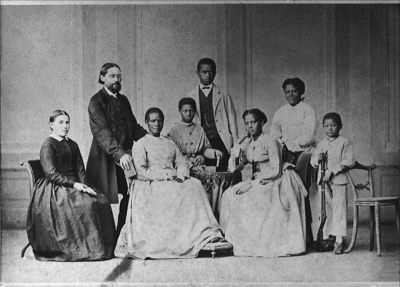 "This is a great 1873 picture and story. Hope this helps someone. Look at her feet atop the little ottoman. Catherine Zimmermann-Mulgrave, the third person from the left, was a survivor of a slave voyage from Africa. She sailed in the slave vessel ""Heroina"". In 1833, the ""Heroina"" embarked slaves in Angola, on the West-Central African coast, and set sail to Cuba, but wrecked off the coast of Jamaica."