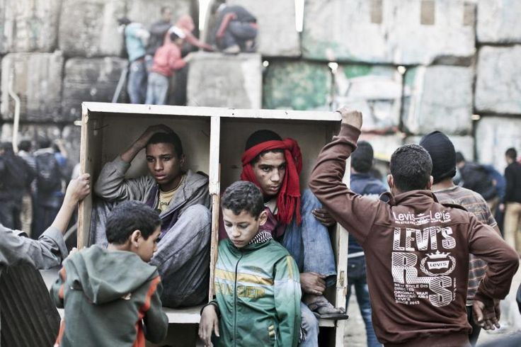 Young protestors take shelter behind a barricade during clashes with Egyptian police on the second anniversary of the Revolution. Cairo, Egypt, Jan. 2013.