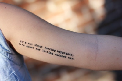 """The lyrics are """"It's not about forcing happiness, it's about not letting sadness win"""" written by Dan Campbell of the band The Wonder Years."""