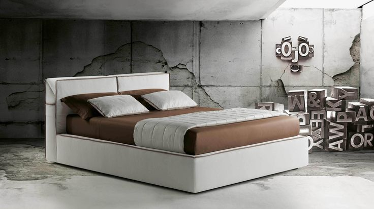 "A #bed with contemporary design, Guadalupe features a comfortable adjustable headrest and a grosgrain edging, which can be designed in various colours. It is available with either a fixed slatted bedstead or with two #storage variations, one a regular storage placed underneath the mattress or with the ""Komodo storage"", which, in addition to the regular storage, contains a practical system that raises the slatted #bedstead and the #mattress to ease the fitting of the bed linen."