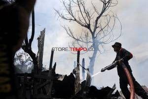 Petugas pemadam kebakaran berusaha memadamkan api yang membakar permukiman padat penduduk di Jalan Kerung-Kerung, Makassar, Kamis, 27 Maret 2014. Kebakaran yang diduga akibat korsleting arus listrik tersebut menghanguskan 15 rumah semi permanen