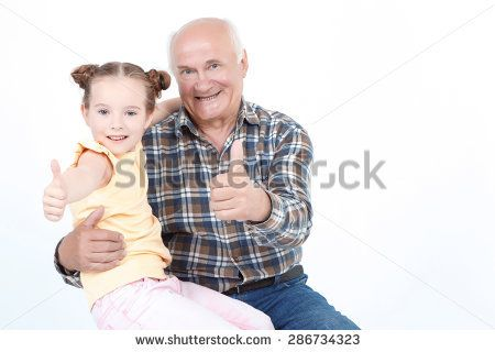 Portrait of a grandfather sitting smiling and holding his small granddaughter on his knees while both showing thumbs up, isolated on a white background