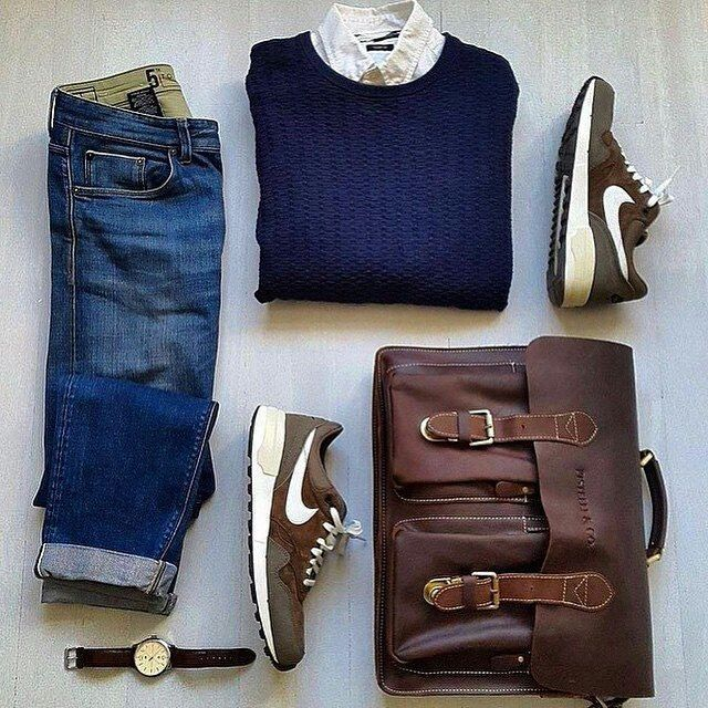 Men's casual outfit m sneakers, jeans, button down, navy sweater, watch, leather messenger bag.