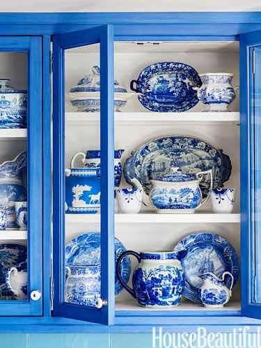 "Collection of blue and white English china artfully displayed in a vivid ""blue to match"" china cabinet.  Lovely."