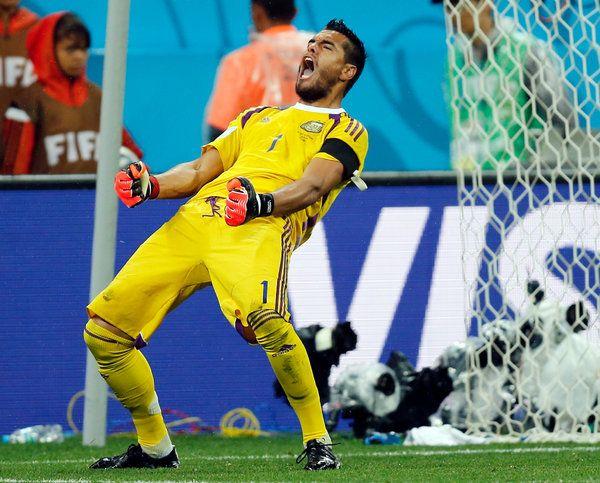 Sergio Romero the Argentina goalie stops a penalty then exalts.