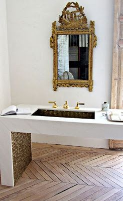 Love this antique gold mirror surrounded by an all white bathroom + vanity with the pop of gold glass tile and wood herringbone floors #glambath