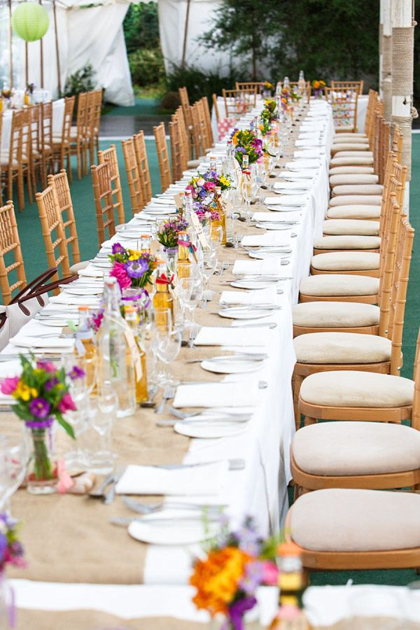 Hessian table runner and flowers in jam jars for a bright and colourful Somerset marquee wedding. Photography by www.photoglow.co.uk