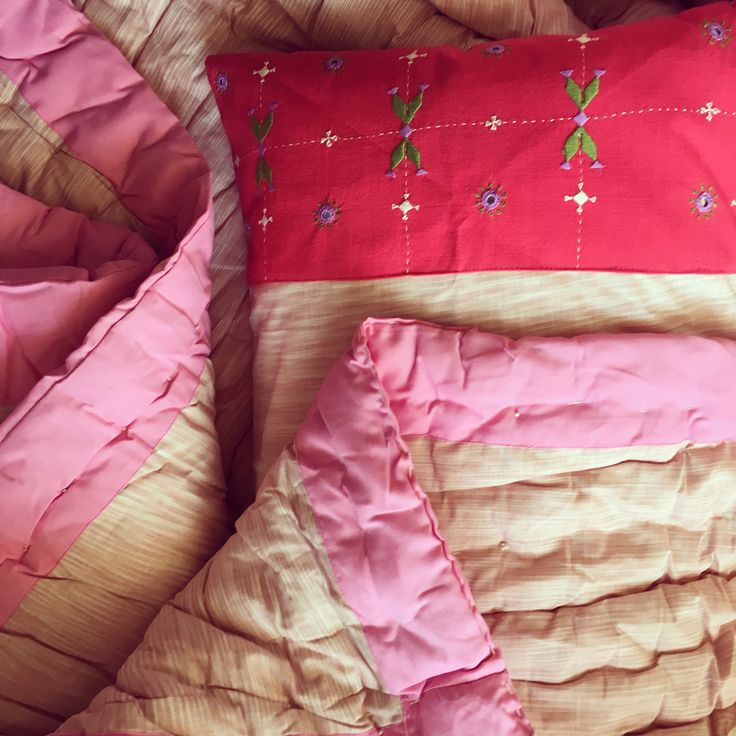 #Organic #cotton filling gives this #handmade #blanket set a cozy natural feel when you tuck yourself in it. The hand #embroidered #pillow covers carry #ethnic motifs and give a contrasting effect with a red patch on #pink background. Available only at Artnique.