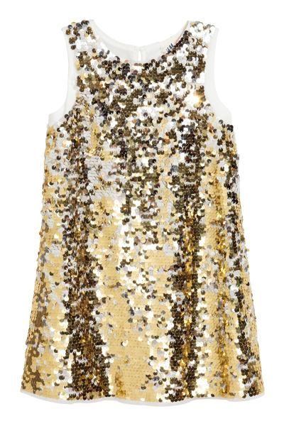 Zomer 17 Een mouwloze jurk van mesh met omkeerbare pailletten (maat 92-98 met gewone pailletten). De jurk heeft een splitje met een knoop in de nek. Gevoerd.