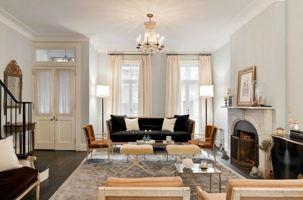 living room similar in size to mine: Lovely NY City living room with pale gray blue walls paint color, navy blue velvet sofa settee, burnt orange pumpkin velvet Greek key chairs, yellow crushed velvet ottomans, grau rug, limestone fireplace and white silk window panels curtains.  Good inspiration. Nate Berkus the-homestead