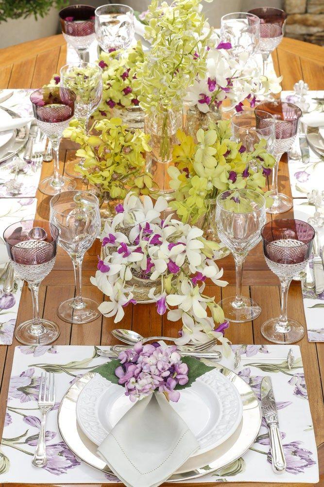 Para compor a mesa, louça branca com bordas trabalhadas em alto-relevo e jogos americanos tulipa em tons de lilás e verde, guardanapos verde-oliva e porta-guardanapos de hortênsia, todos da nossa marca Couvert.