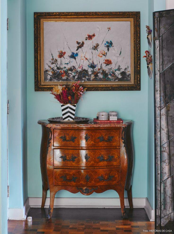 Hall de entrada com cômoda vintage, parede verde água e decoração com clima Boho.