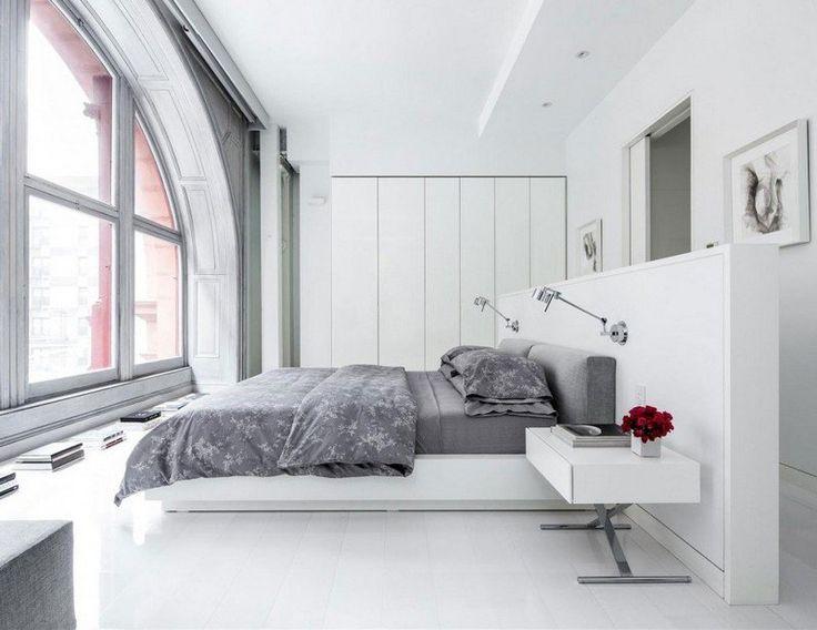 chambre adulte avec un grand lit et table de chevet blanc
