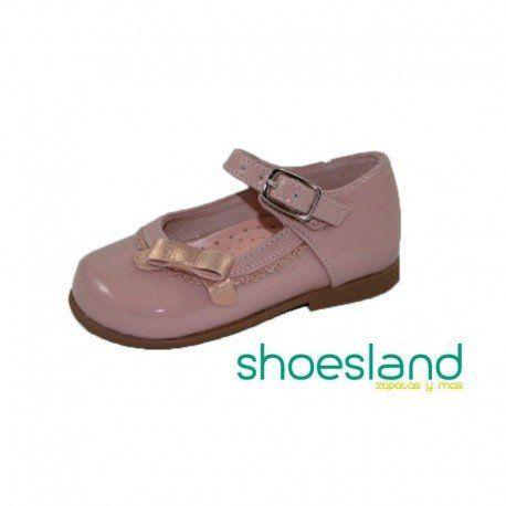 Zapatos clásicos para los primeros pasos de tu niña tipo merceditas abrochados con hebilla en dulce charol color rosa de Puppets Shoes  Los detalles de festones y lazo en rosa le dan un encanto especial  Del 19 al 24