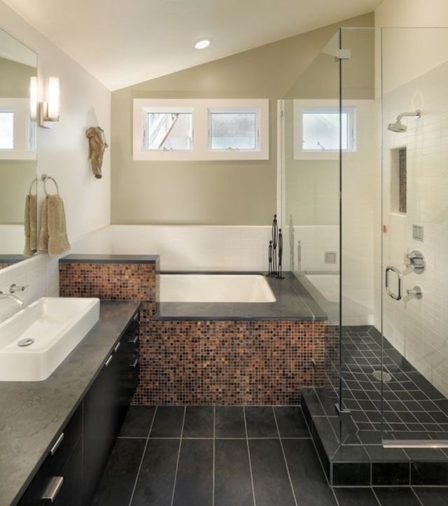 un carrelage de sol noir et une baignoire élégante dans la salle de ...