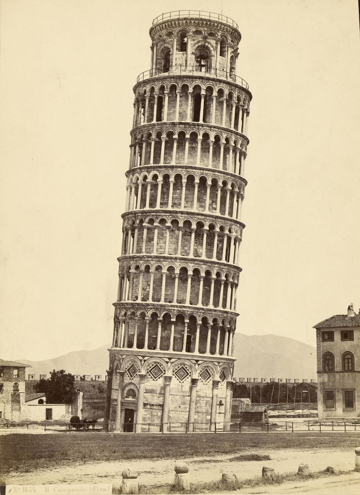 A portrait of the leaning bell tower of Pisa Cathedral. A horse-drawn carriage is parked in the shade beside the entrance to the tower. 1870