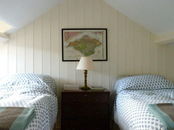 In the attic bedroom, Pentreath added a wall of beaded-board paneling to cover a projecting chimney breast at the same time as creating a cabin feel in the room.