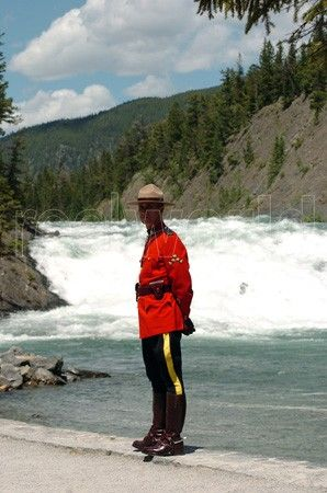 An RCMP officer poses in traditional uniform at the Bow falls in Banff National Park, Alberta