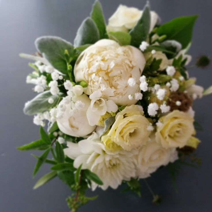 Classical wedding bouquet with white and cream flowers: peaonies, roses and eustoma.