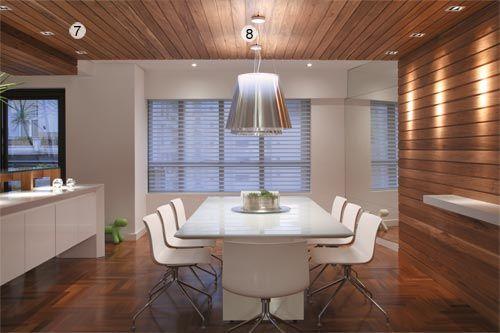 """7- Na sala de jantar, os designers capricharam nos detalhes de iluminação. É que aqui, um grande painel de MDF revestido de folhas de freijó delimita o ambiente e é um elemento dominante na decoração. Nas extremidades do painel, três lâmpadas embutidas AR 48. """"Elas são densas, bem focadas. Em um lado, iluminam o painel e, no outro, o foco é sobre o balcão"""", explica o arquiteto.8- Para contrastar com o tom escuro da madeira, foi usado mobiliário totalmente branco. Sobre a mesa, duas…"""