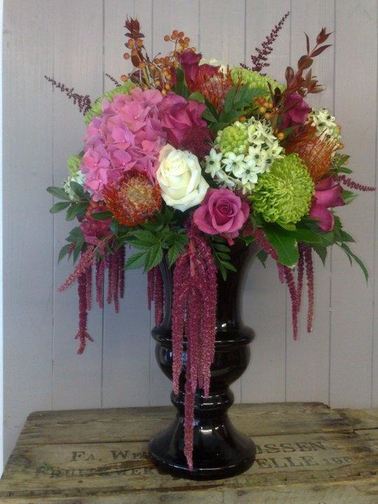 Garden urn arrangement of hydrangea, fuji mums, roses, protea, star of bethlehem, and amaranthus