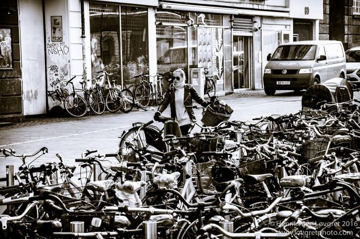 A young girl, picking up her bike from the bikestand.