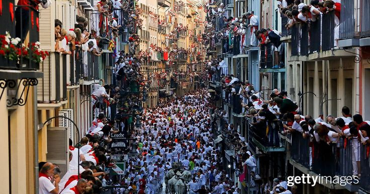 """Revelers run with Fuente Ymbro's fighting bulls along Estafeta St. during the second day of the San Fermin Running of the Bulls festival on July 7, 2016, in Pamplona, Spain. The annual Fiesta de San Fermin was made famous by the 1926 Ernest Hemingway novel """"The Sun Also Rises."""" #2016InFocus"""