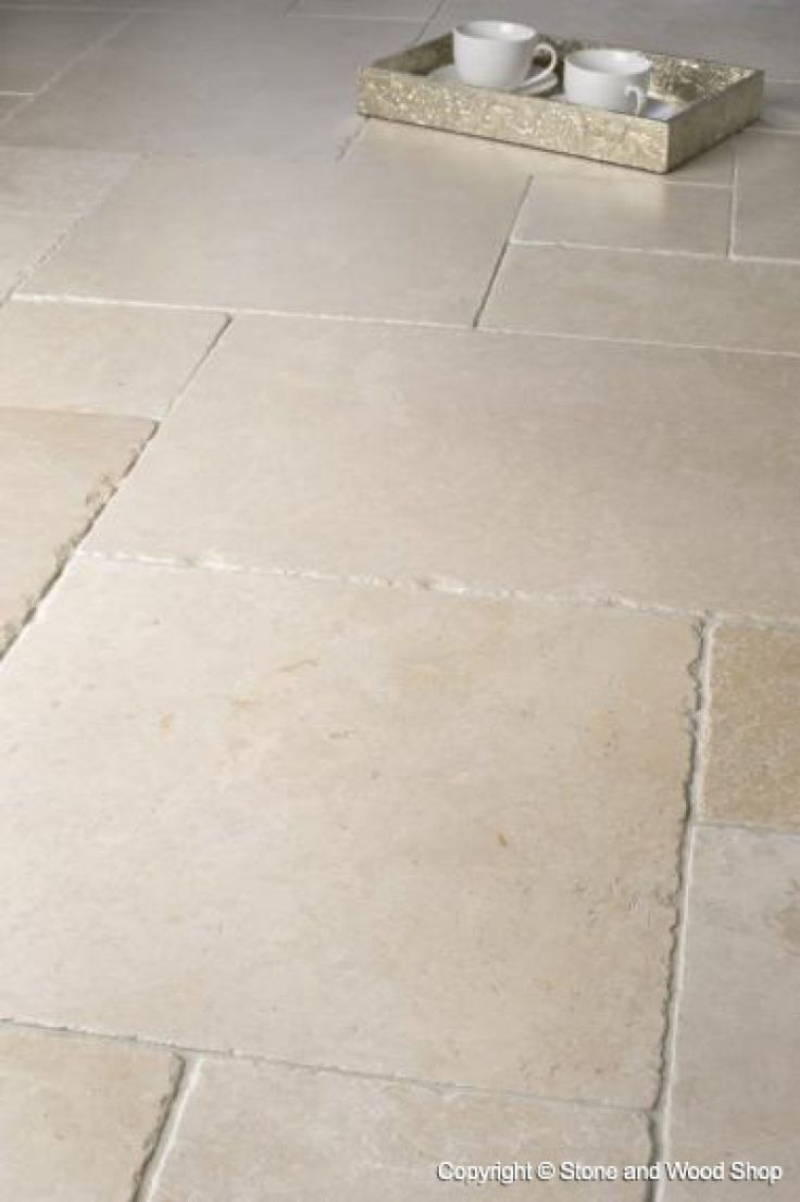 Een lichte natuurstenen vloer met onregelmatig gevormde tegels in ...