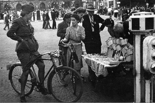 26 août, Paris est libre et le peuple acclame le général De Gaulle. Trois joursplus tard, lestroupes américaines défilent sur les Champs-Elysées. Enfin, Paris revit : les rues se remplissent, les Américains profitent des joies retrouvés de la capitale et les drapeaux de la victoire sont vendus un peu partout, comme ici, place de l'Opéra.