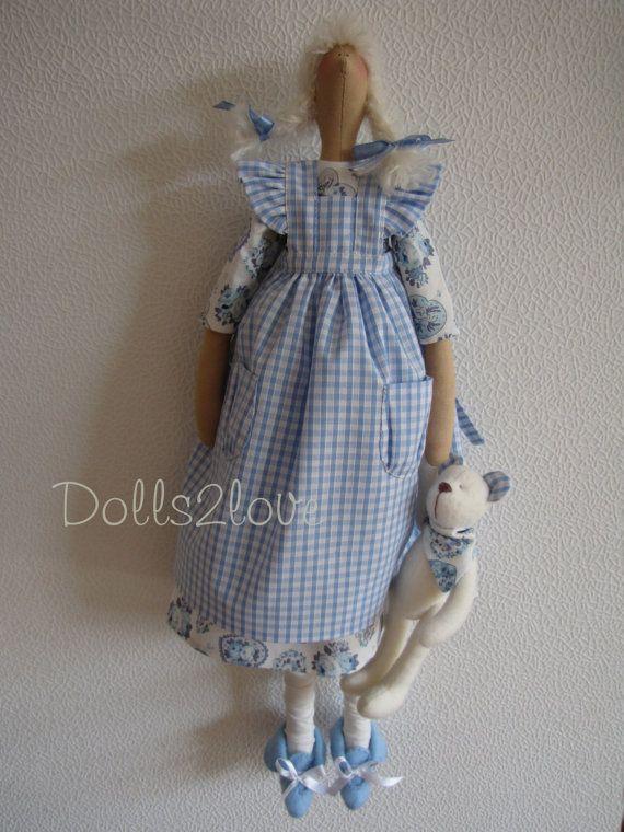 Tilda boneca Brittany usando um vestido com estampa ,avental e sapatos de feltro, acompanha ursinho