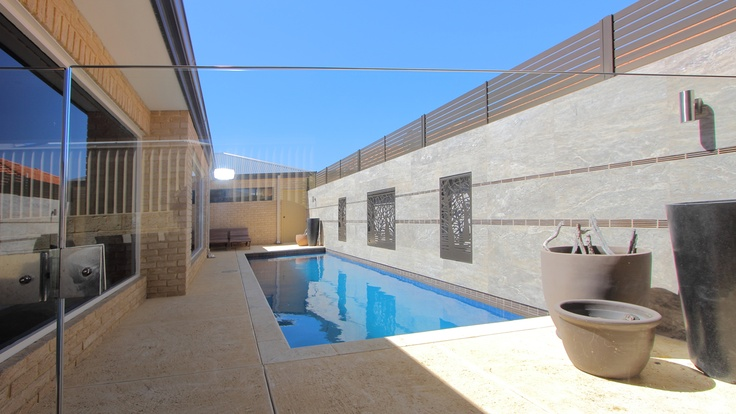 Travertineand laser cut steel provide a magnificent backdrop for an inviting pool