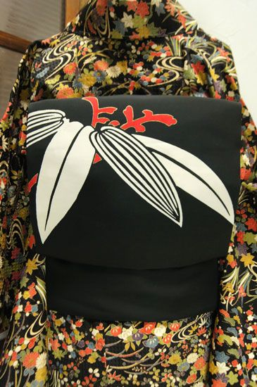 深い紅色と白がきりりと映え、金の縁取りが品の良い華やぎを添える笹の葉模様が大正浪漫・昭和レトロな詩情をさそう名古屋帯です。