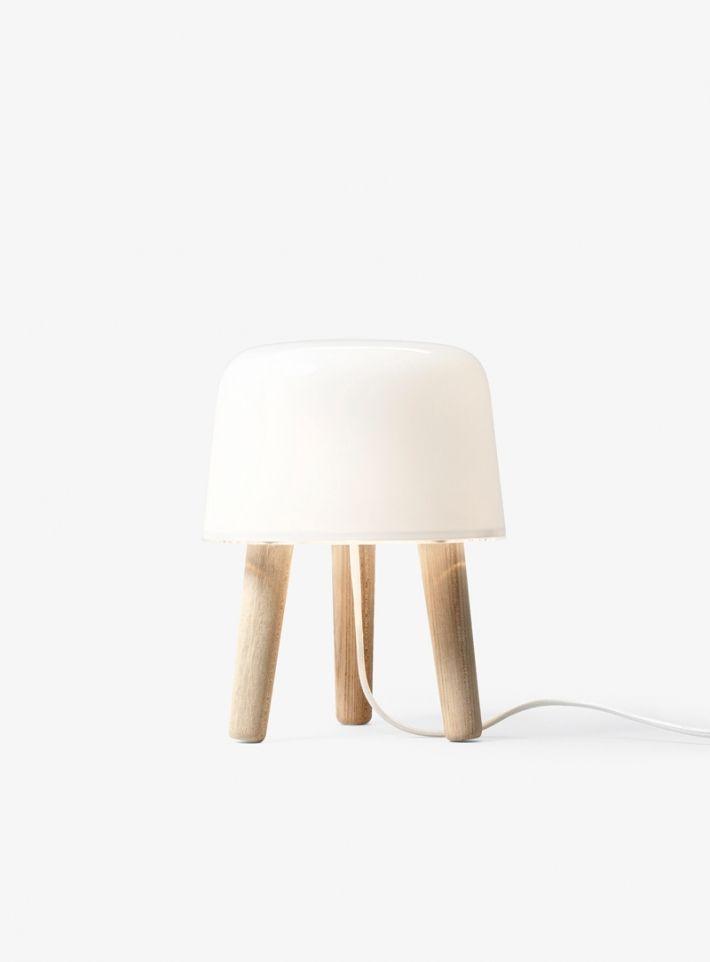 Milk NA1  Mit Milk verwandelten die Designer von Norm Architects den traditionellen Melkschemel in eine Tischleuchte perfekter Größe und Proportionen, die ein angenehm warmes Licht spendet. Die Kombination aus Opalglas und Massivholz bringt eine Aura der Natürlichkeit sowie die Wärme reduzierter, skandinavischer Einrichtungsgegenstände in den Eingangs-, Wohn- oder Schlafbereich. Ein schönes Detail: das textilummantelte, farblich auf die Leuchte abgestimmte Kabel.