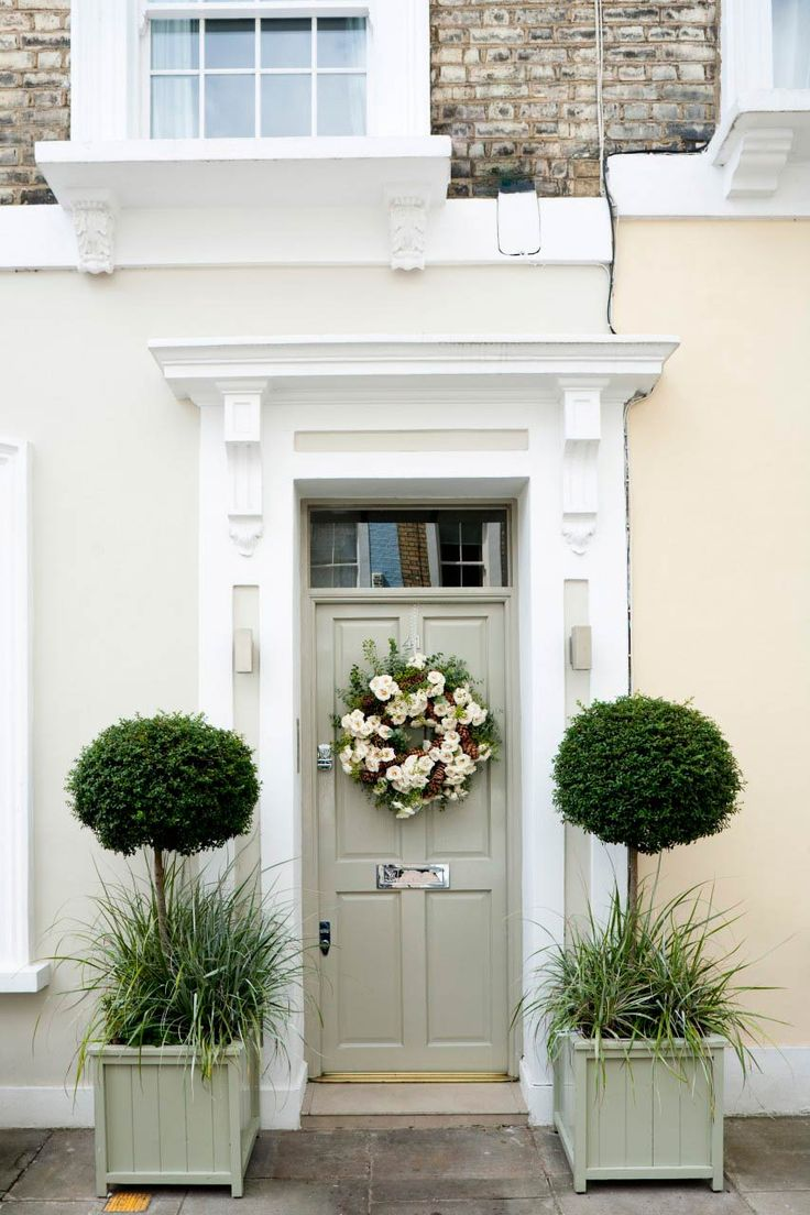 A beautiful Georgian house exterior with green panelled front door, a Christmas wreath and matching green wooden planters. Homes & Gardens December 2009. Photographer Mark Bolton. #Country #Decorating #Festive