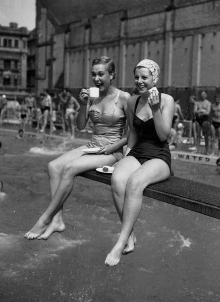 22 August 1955: Two office workers choose the diving board at the Holborn Oasis swimming pool in London as the coolest place to eat their lunch during the heatwave