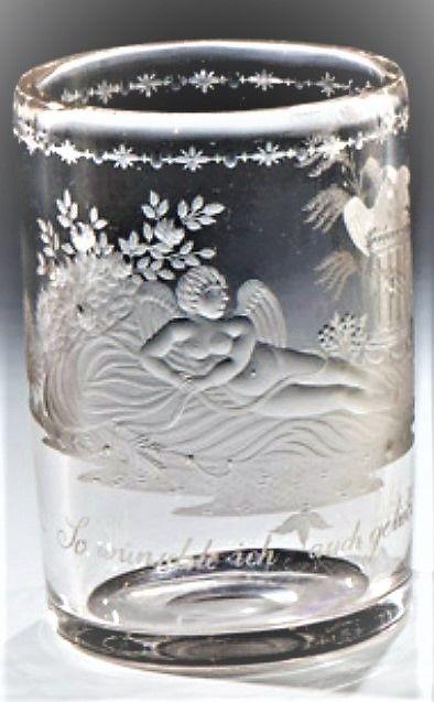 Hieronymus Hackel (zugeschr.), um 1830 Graustichiges Glas mit ausgeschliffenem Abriss. Frontal in feinem, teils geblänkten Tiefschnitt ausgeführter Dekor: Liegender Amor mit Attributen, einem, auf einem Podest sitzenden Taubenpaar zusehend, im Hintergrund Rosensträucher und exotische Bäume. Darunter Inschrift: ''So wünschte ich auch geliebt zu werden''. Unterhalb des Lippenrandes ornamentale Bordüre. H. 10,3 cm