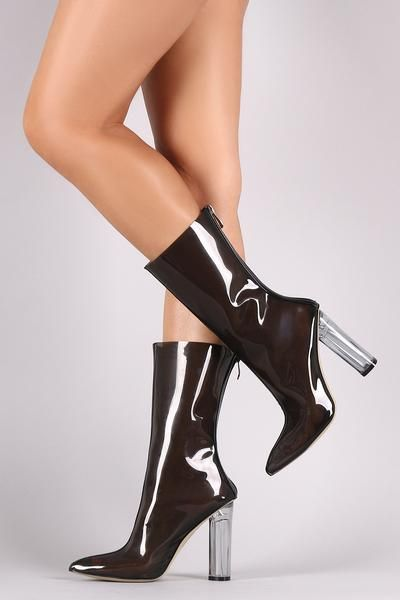 These trendy mid calf boots feature a sheer lucite upper with patent leather trim, center stitched details, pointy toe silhouette, and architectural clear round heel. Finished with cushioned insole an