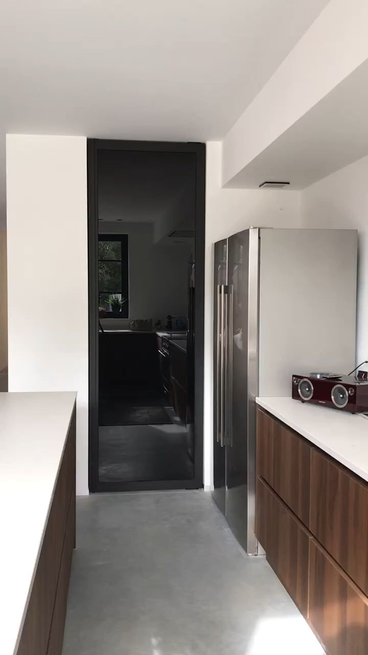 Glass pivot door with black anodized profiles and Dark Grey coloured glass.