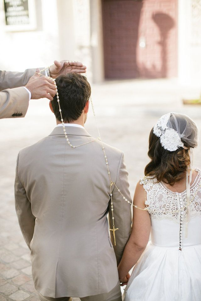 """As part of the ceremony to symbolize unity, a large loop of rosary beads is placed in a figure eight shape around the necks of the couple after they have exchanged their vows. The specially appointed 'padrinos' are in charge of lassoing the couple together. The lasso is then gifted to the bride as a souvenir of her taking the groom's hand in marriage & symbolizes their commitment to each other."""