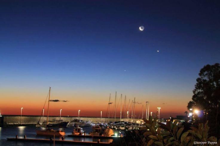 6 febbraio 2016. Congiunzione Luna-Mercurio-Venere di Giuseppe Pappa.  Congiunzione tra Luna,Venere e Mercurio ripresa al porticciolo di Ognina di Catania all'alba del 6 Febbraio 2016 con una canon1100d e treppiede. Singolo scatto di 6s