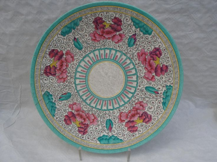 A 1940s HJ Wood Bursleyware large wall plaque, designed by Charlotte Rhead in an unrecorded pattern, having a tube-lined decoration of flowers and leaves in shades of pink and green, within a greek key border, on an mottled grey ground, printed marks verso to include the bespoke 'Arabesque by Charlotte Rhead' stamp, 41cm diameter