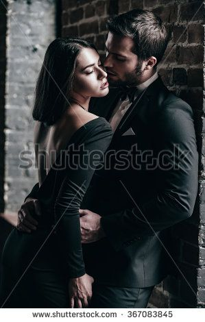 Real passion. Beautiful young loving couple bonding to each other while both standing against brick wall indoors
