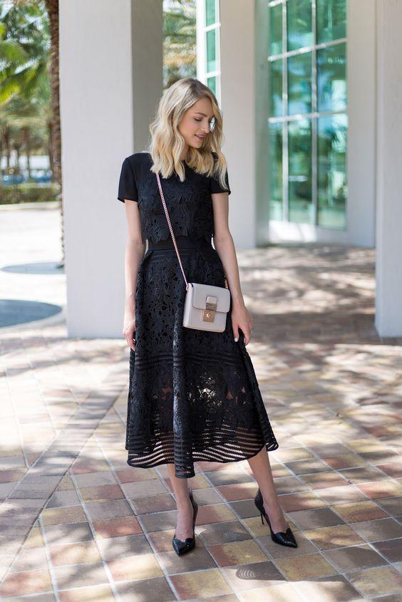 Модель в черном кружевном платье миди, туфли лодочки и белая сумочка