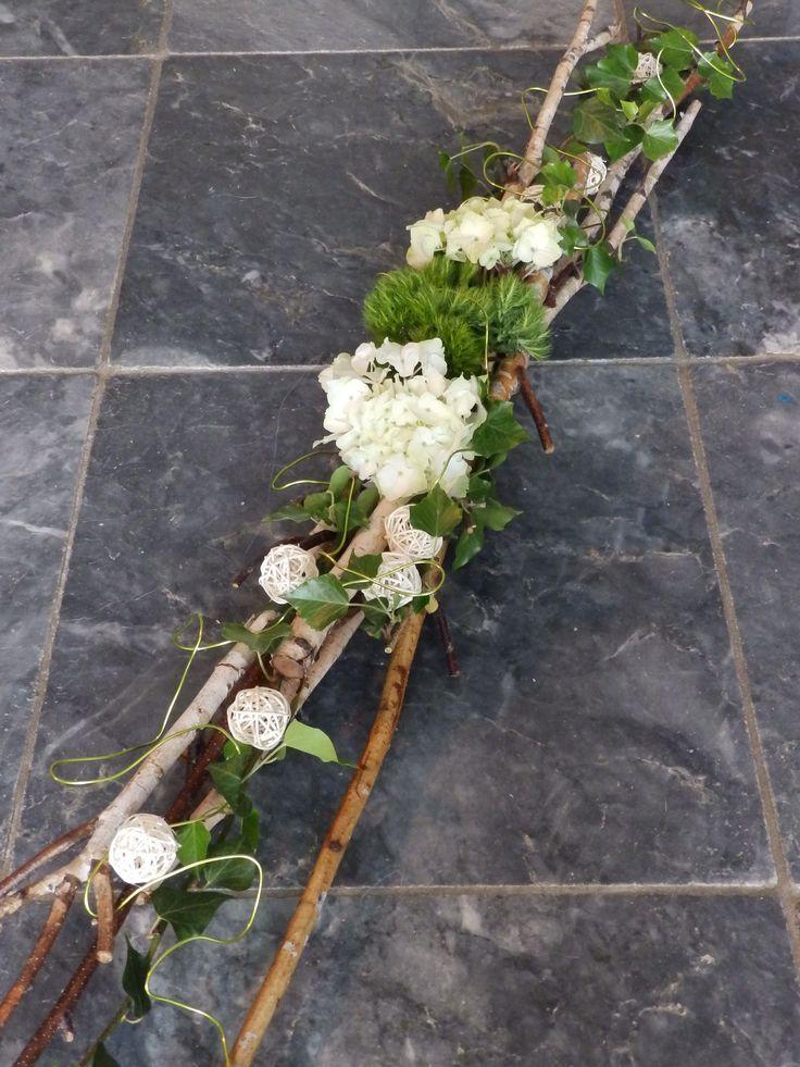 langwerpig rouwarrangement op berkentakken met witte hortensia
